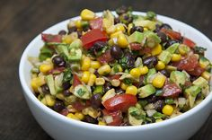 1 15.5 oz can black beans, rinsed and drained  9 oz frozen (or canned) corn, thawed  1 tomato, chopped  1 avocado, chopped  1/4 cup red or white onion, diced  1 scallion, chopped  1 lime, juice of  3 tbsp extra virgin olive oil  1 tbsp cilantro, chopped  salt and fresh ground pepper  Mexican chili powder, a few pinches