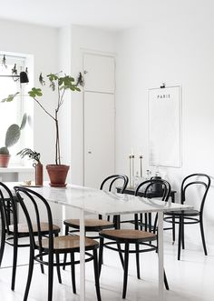 Marble table, natural/wood/black chairs.