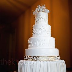 To incorporate the couple's theme, the four-tiered wedding cake was decorated with hand-painted lace designs and Spanish words like amor.
