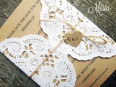 """Simply Lace""A lovely and simple Save the Date card or Wedding Invitation , this gorgeous card is handmade created using 230gsm Recycled card stock, wrapped with a lacy doily which is adhered to the backing of the card, and finished off with natural twine and a heart tag with the bride and groom's initials. Invites accompanied by textured ivory envelopes. The ProcessSend us a convo or email (josephine@misiu.com.au) with the following informati..."
