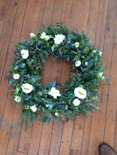 Fresh sympathy wreath mostly greens some white flowers