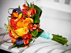 Bouquet for Becky.  Orange gloriosa, yellow roses, bear grass, tropical by Love Is In The Air.  www.loveisintheairevents.com