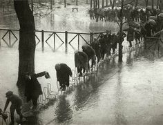 People walk across a row of chairs to avoid flood waters in Paris, 1924 Historical Times