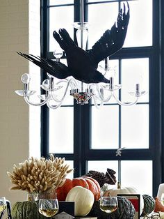 Flying Overhead - great idea for Halloween decor: a raven attached to the chandelier like it's flying overhead.  Now that will create a spooky dinner party!