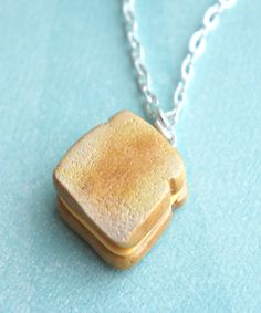 this necklace features a handmade grilled cheese sandwich pendant sculpted from polymer clay. it measures approx 2 cm x 1.5 cm. it hangs on a silver tone chain necklace that measures 24 inches in leng