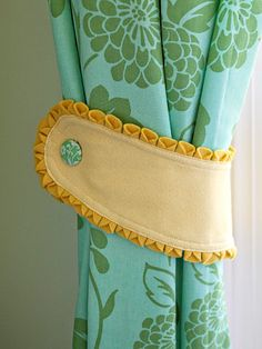 Cute Curtain Tieback. Well I changed mine some. I used a decorative trim on the bottom only and used fabric instead of felt. However, this was my inspiration and I made tiebacks all by myself!