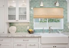 Seafoam Green Subway Tile Backsplash. Kitchen with white cabinets and Seafoam Green Subway Tile Backsplash. White industrial sconces are mounted on green subway tiles framing a window dressed in a bamboo roman shade hung above a farmhouse sink with a polished nickel faucet fixed in a marble countertop complementing white inset cabinets finished with polished nickel pulls as upper glass front cabinets are lit by custom lighting. Seafoam Green Subway Tile Backsplash #SeafoamGreen…