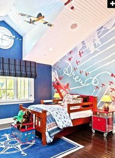Flying High  Making the most of the high ceiling of this boy's room, designer Sue Firestone of Smith & Firestone Associates creates a airplane-themed space with dark and light blue walls, hanging model airplanes and a mural featuring the child's name written across the sky.