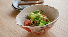 This picture is smoked salmon and fresh vegetable in the bowl made by Noritomo Suzuki painted by red color  Since the picture drawn inside this bowl is gentle, you may use for what kind of dish.