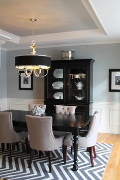 Pale blue dining room walls and ceiling with white wainscoting, black accents