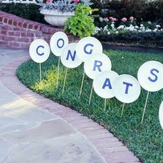 Wooden Sign Graduation Party. Direct your guests with this wooden sign to your front walk. Cut letters from blue paper and glue to paper plates. Attach wonder dowels and stick into the lawn for simple graduation party decor without costing too much.