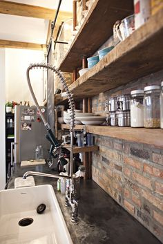 Customized kitchen with reclaimed barnwood for the kitchen shelving, island cladding all fabricated by builder  Builder:  design-build loft in wicker park, utilizing reclaimed materials and working with the clients to achieve their desired sense of style  Photo by Clayton Hauck for Builder