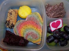 A colorful heart sandwich, a babybell with a sun cut into the wax, homemade berry fruit roll up, a chewy granola bar, black and green gr...