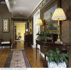 entry hall: view to dining room, wallpaper and border, traditional demi lune hall table with lamps, cahepot with house plants, pictures, oriental runner, parquet floor