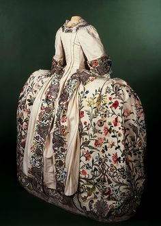 Mantua, 1740-45, Embroidered silk with colored silk & silver thread. Court dress was an exclusive & ornate style of clothing worn by the aristocracy who attended Court. The style is based on the 17th-century mantua. The shell, the quintessential Rococo motif, constitutes the basis of the embroidery pattern. Leafy scrolls, latticed arcades and tassels are also featured, as well a profusion of realistically rendered flowers worked in a variety of coloured silks in satin stitch & french knots.
