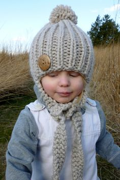 READY TO SHIP: Knit Tan Ribbed Children's Hat with Knit Side Ties, Pom Pom Top, and Over sized Wood Button - Knit Toddler Hat. $23.00, via Etsy.