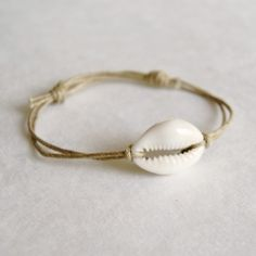 Simple twine and shell adjustable bracelet with sliding knots.  Full tutorial.