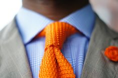 Beige jacket, blue plaid shirt, orange knit tie