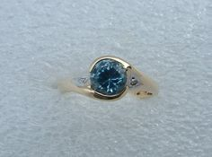 Blue Topaz and diamond ring. A round blue Topaz has two side diamonds set in a manner to highlight them as well as the topaz.  The ring is made with 9 carat yellow gold. The Topaz is 5.5mms in diameter.  This ring is simple and elegant and comfortable to wear all day.  Ring size is L (51/2) but can be resized free of charge. Contact us before placing order.  The ring is available to ship in 1-2 working days. Please allow a couple of additional days for resizing.  This ring can be made in…