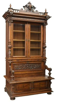 "French mahogany/walnut bookcase bench, c. 1900, having a figural and mask arched cornice over a stepped frieze and two glazed doors opening to shelves, the lower hinged bench seat with scrolled arms and a foliate carved storage back and pull out tray, rising on the paneled base with bun feet, joinery includes mortise, tenon and dovetailing, 104""h, 54""w, 31""d .*"
