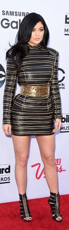 Who made Kylie Jenner's gold stripe dress and black sandals?