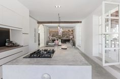 Spanish kitchen featuring concrete bench tops and floors and stone feature wall. Felinity, Spain. Renovation by munarq