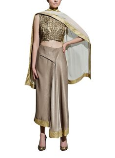 Kanelle pioneers the meaning of fusion with this alluring gilded outfit. It features a cropped golden blouse that is fully embellished. Metallic bead and spike detailing adorn the blouse. Paired with the top is a dhoti-style draped skirt with a gold metallic border. Completing the look is a sizzling stole with a golden border.