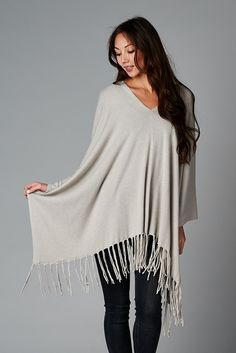 Our super soft vneck  easy fit poncho with fringe hem. This is a one size fits all and a versatile piece for travel and nights out on the town. Our poncho is made of 25% viscose, 55% nylon and 20% modal and we recommend dry cleaning.