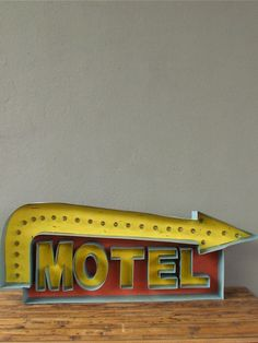 """drawing on the era of early motorways, this recreated vintage-inspired metal motel sign will set your home decor to a jaunty pace. in a pale aqua casing, the rust-to-coral red back drop + yellow graphics are a soft twist on a primary palette. complete with bulbs that light up in a constant glow. perfect for a game room, or well suited to a tongue-in-cheek commentary on how busy your home feels, let the arrow point the way to a little light hearted nostalgia.  dimensions:6""""d x 51""""w x 19""""h"""