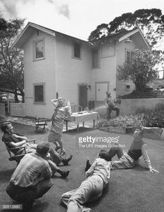 Actor Charles Laughton (R) spraying his wife Elsa Lanchester (C) with the water hose at their weekend cottage.