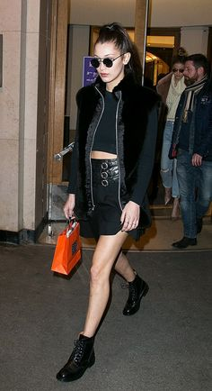 Bella Hadid wears a shearling jacket, crop top, miniskirt, and lace-up boots