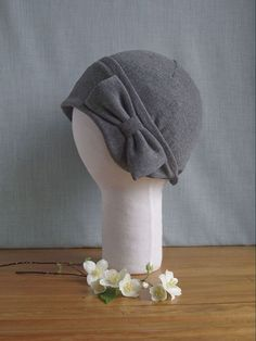 This cloche will be made to order to your preferences. I make these cloches from jersey knit so it stretches and fits snugly to your head. Because it is sweat-shirting it wont get itchy like acrylic or wool. You can wear it all day, staying warm and looking cute! It comes right down over your ears, protecting them from the wind and cold.  There will be a large bow made of the same fabric over the left ear.  There are a few size options: SMALL - is good for children, or if you have a little…