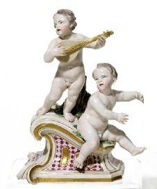 Musizierende Putten auf Architekturstück. Frankenthal. Um 1770. Modell J. W. Lanz. Porzellan, farbig und gold staffiert. Höhe 19 cm, Länge 15 cm.