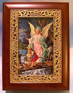 "Exclusive! Beautiful Wooden Musical Box with picture of the Guardian Angel surrounded by elaborate gold frame border. Box is lined with velvet and plays ""Ave Maria"". Gift Boxed."