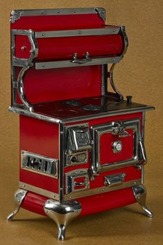 Reproduction Karr Range Co. enameled, iron, and tin toy cook stove with a red surface and nickel trim, 21'' h., 12 1/2'' w.