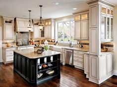 """Desi:  Love the overall look ,but this could have been done much better.  The backsplash is just way too loud and variegated.  However, it is a reasonable example of what off-white cabinets, black island, light granite, and scraped wood floors would look like.  Does Tim like this floor?  Probably not the color I would pick on it's own, but the tone seems to go well with the cabinets.  Noticing that the black island adds an """"edge"""", while matching off-white island is more classic."""
