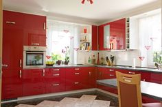 This rich kitchen design sports glossy red cabinetry from floor to ceiling, highlighted by brushed metal hardware. Dark granite countertops and white walls add contrast, while window shades nod toward the cabinetry with red triangle designs.