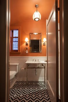 Chic bathroom with black and gray marble chevron tiles accented with geometric inset tiles floor along with subway tiled half wall below bright orange walls and ceilings.