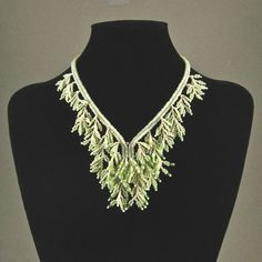 Seed beads and crystals come together to make this charming fringed necklace. The neck strap is woven from gold-lined cream colored seed