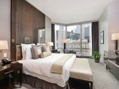 Floor-to-ceiling wooden headboard fits the urban feel of this skyline  penthouse.