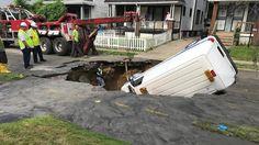 Ein Abschleppfahrzeug birgt in Cleveland (USA) ein Fahrzeug, das in ein sich plötzlich auftuendes Erdloch gestürzt ist.