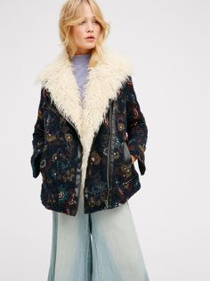 Jacquard Wool Coat With Faux Fur   Jacquard wool coat with a pretty floral print and ultra cool faux fur detail around the collar. Front exposed zipped pocket and side hidden pockets. Zippers at the sleeve cuffs. Warm inner lining perfect for the cooler months. Adjustable snap button sides.