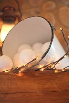 "made these snowballs by dipping syrofoam balls into a bowl of watered-down white glue and then rolling them in another bowl of clear glitter. We used bamboo skewers (sticks) to hold onto them and stuck them into a block of styrofoam to dry. The glitter will get clumpy from the glue…but that's good, it give the ""snowballs"" a more realistic look."