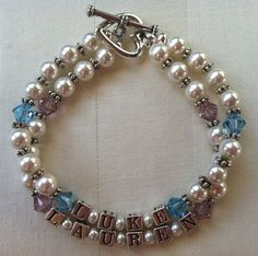 A classic Mother's Bracelet in white Swarovski pearls. This bracelet is made with silver-plated block letter beads with the names of your choice, four birthstone Swarovski crystals per strand of your choice, white Swarovski pearls, silver daisy spacers, and a heart toggle clasp.    http://www.etsy.com/listing/93302022/double-pearl-strand-mothers-bracelet