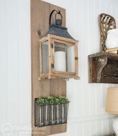 Farmhouse style lantern hanging from a diy wood plaque