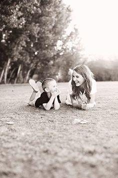 Chica sentada en el pasto junto a su hijo pequeño