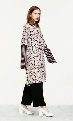 The loose fitting Lidia dress is made of viscose crepe in the black, off white and pink Unikko pattern. It has three-quarter length sleeves that are dropped at the shoulder, a straight cut to the knee length hemline, and a detachable belt. Marimekko, Color Combinations, Hemline, Off White, Bell Sleeve Top, Fashion Outfits, Coat, Sleeves, Pink