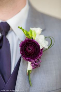 Purple ranunculus buttonhole on grey suit