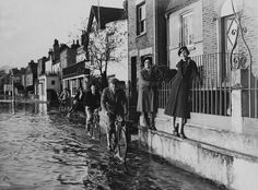 Men cycle through the flood water as the two ladies attempt to stay dry as the Thames floods at Strand On The Green, Chiswick, Old London, West London, Richmond Upon Thames, Brentford, River Thames, London Photos, Old West, Vintage Photos, Chelsea