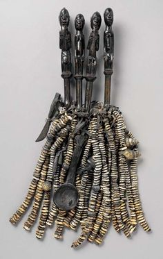 Africa | Eshu ritual object from the Yoruba people of Nigeria | 20th century | Wood, cowrie bells, leather, spoons, knives, small wooden discs, brass bells and other objects.